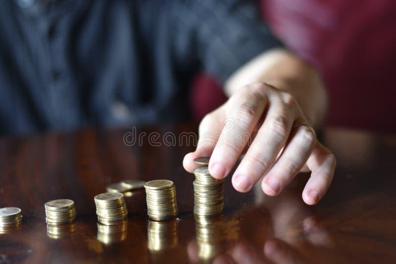 Hand av den Caucasian mannen som staplar mynt royaltyfri bild