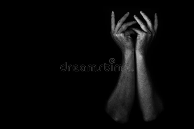 Hand av den deprimerade och hopplösa mannen bara i mörkret royaltyfri bild