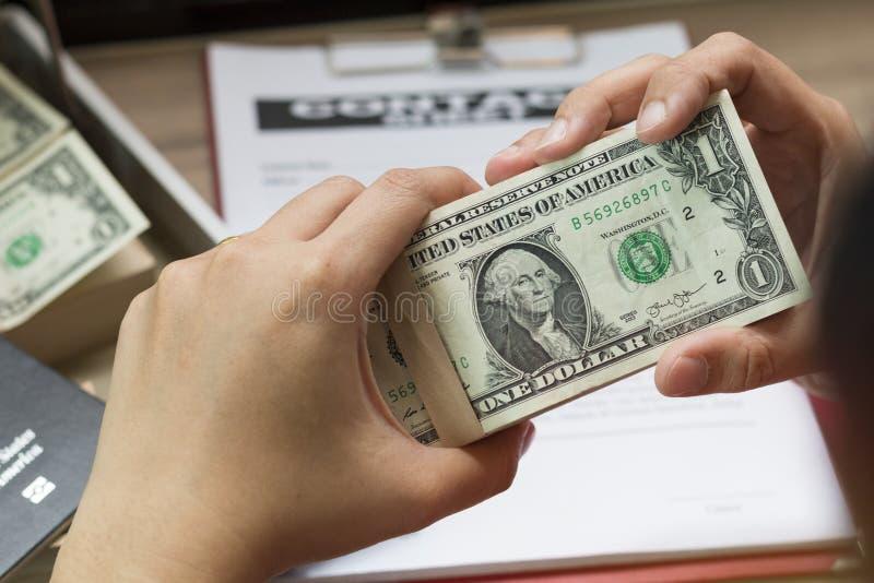Hand av den hållande dollarräkningen för affärsman nära affärsdokument arkivbilder