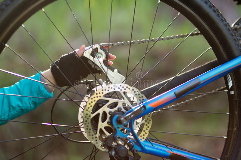 Hand av den kvinnliga cyklisten som reparerar mountainbiket royaltyfri fotografi
