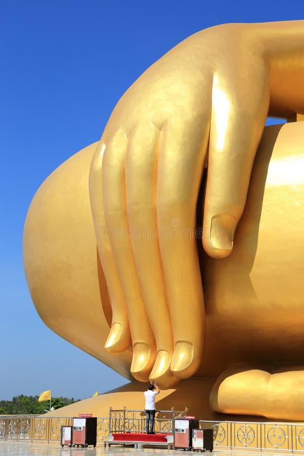 Hand av den största guld- buddha statyn på bakgrund för blå himmel fotografering för bildbyråer