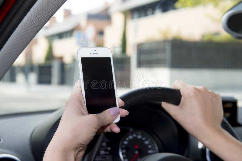 Hand av den styrninghjulet och mobiltelefonen för kvinna som det hållande kör bilen, medan smsa som distraheras i risk royaltyfri fotografi