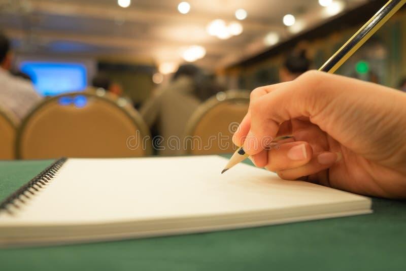 Hand av den unga blyertspennan för innehav för affärskvinna med den tomma anteckningsboken royaltyfri foto