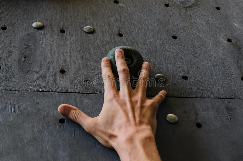 Hand av den unga mannen på en krok av den konstgjorda klättringväggen arkivbild
