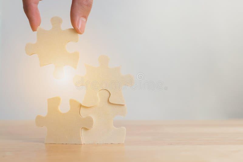 Hand av det manliga eller kvinnliga sättande pusslet som förbinder på träskrivbordet, strategisk ledning royaltyfria foton