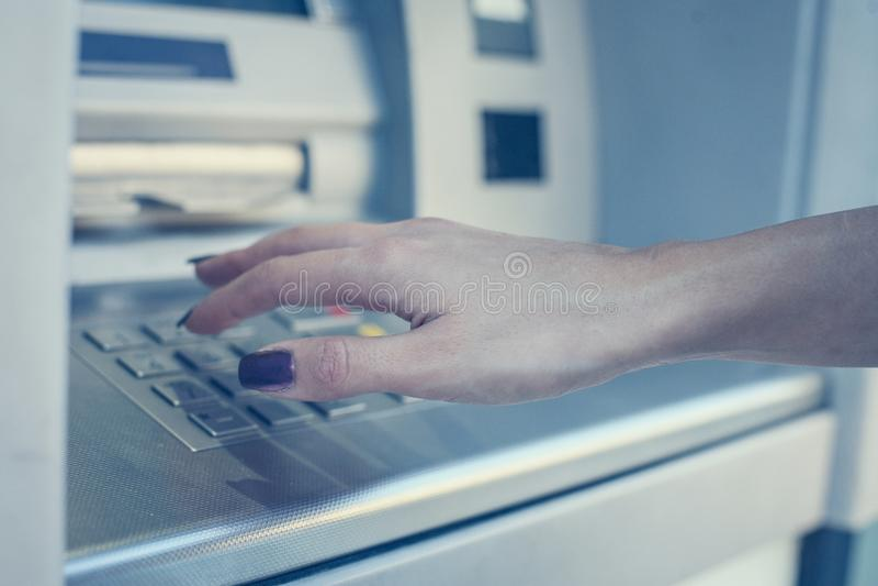 Hand av det trängande tangentbordet för kvinna på den lokala bankomaten royaltyfri foto