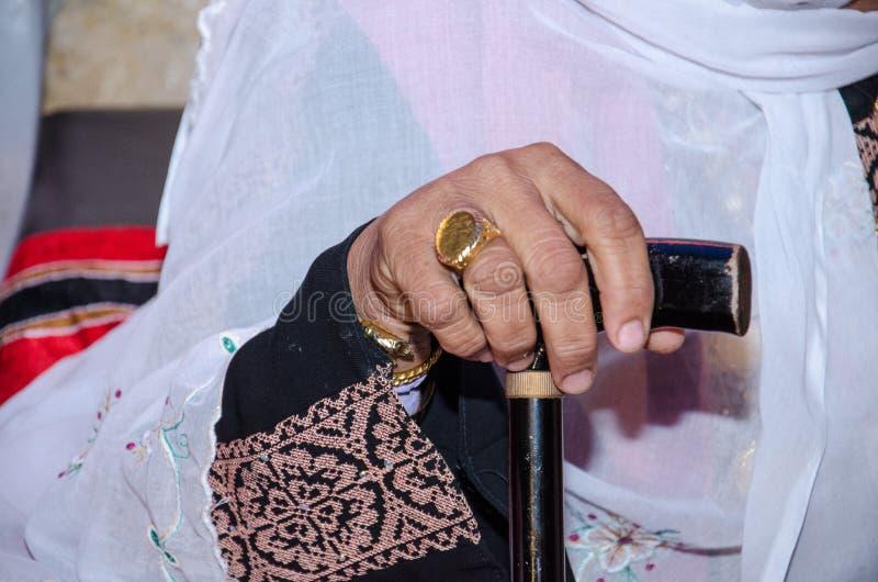 Hand av en äldre kvinna i traditionella beduinkläder med broderi som baseras på en pinne för att gå royaltyfri foto