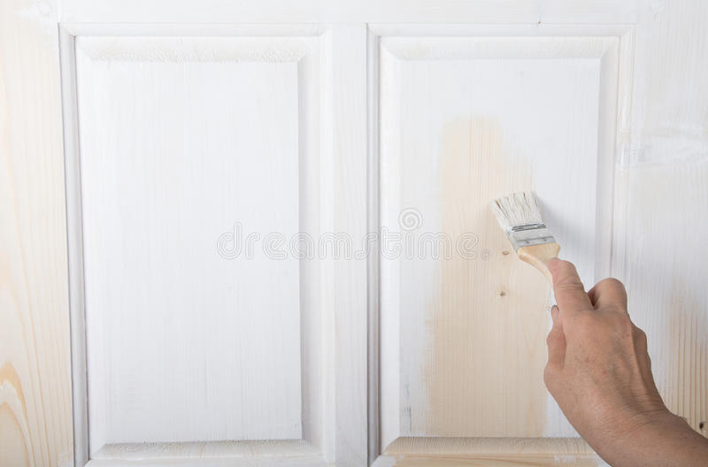 Hand av en äldre kvinna med en målarfärgborste med den vita målarfärgdooen arkivfoto