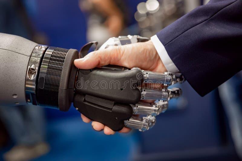 Hand av en affärsman som skakar händer med en Android robot arkivfoton