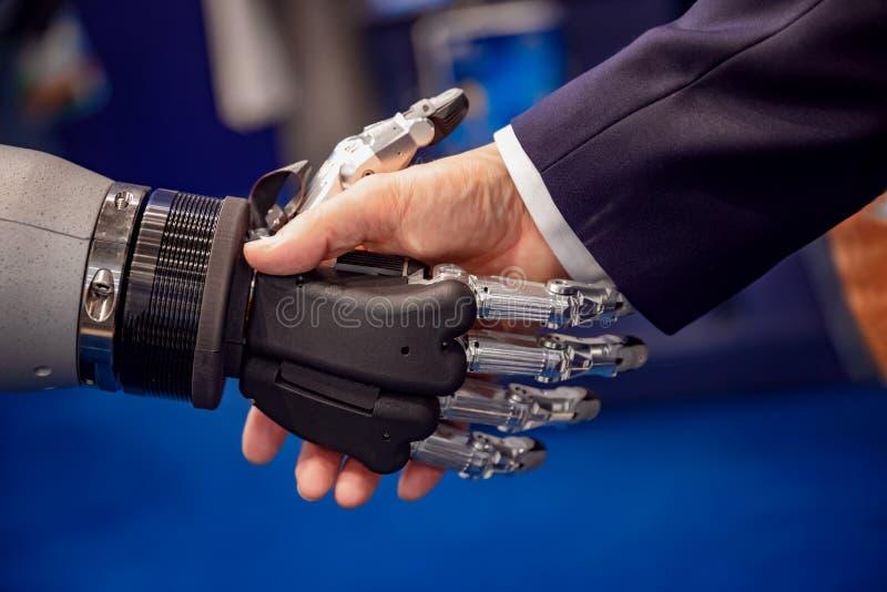 Hand av en affärsman som skakar händer med en Android robot royaltyfria bilder