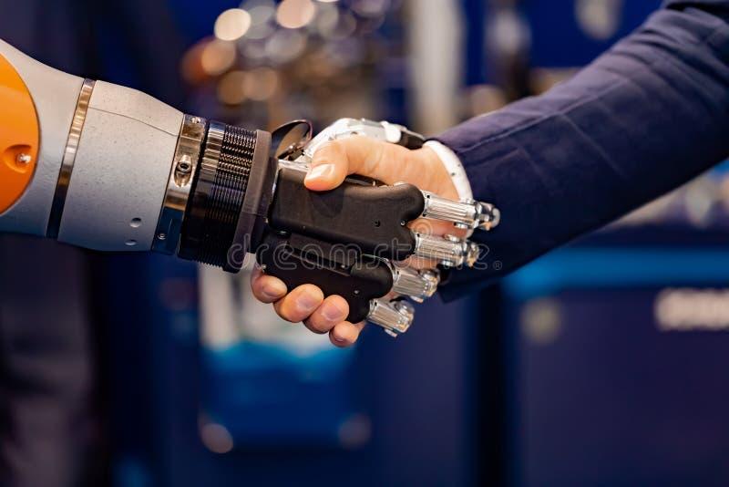 Hand av en affärsman som skakar händer med en Android robot royaltyfri bild