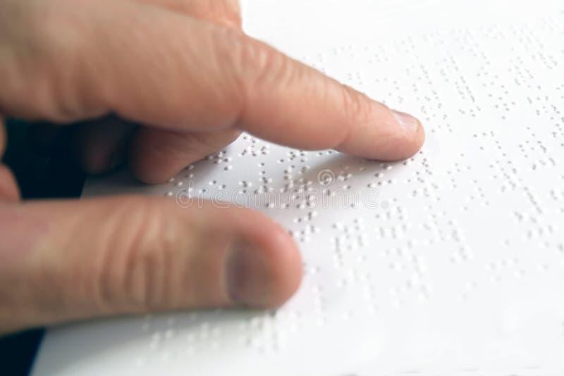 Hand av en blind person som läser någon blindskrifttext som trycker på lättnaden tomt kopieringsutrymme royaltyfria bilder