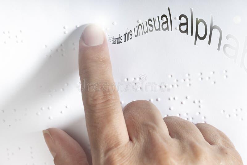 Hand av en blind person som läser någon blindskrifttext som trycker på lättnaden royaltyfri fotografi