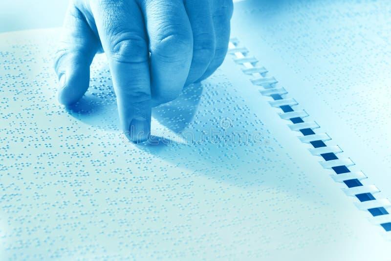 Hand av en blind person som läser någon blindskrifttext som trycker på lättnaden Duotone royaltyfri bild