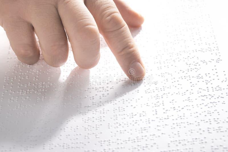 Hand av en blind person som läser någon blindskrifttext som trycker på lättnaden horisontal arkivbild