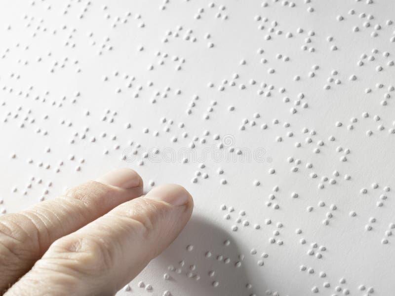 Hand av en blind person som läser någon blindskrifttext som trycker på lättnaden Tomt kopieringsutrymme för redaktör royaltyfri fotografi