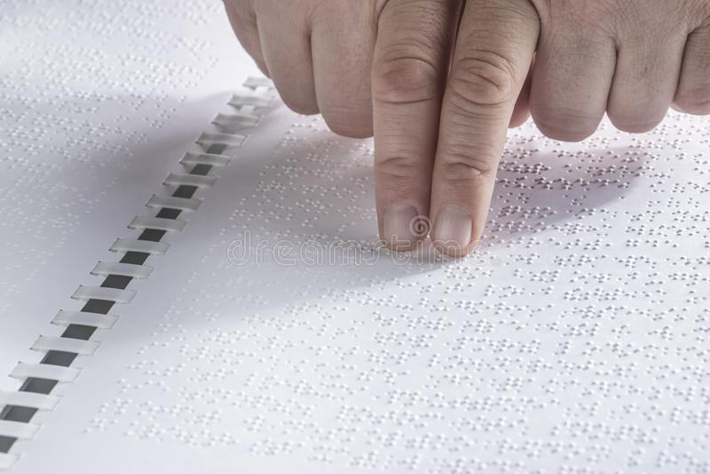 Hand av en blind person som läser någon blindskrifttext som trycker på lättnaden Tomt kopieringsutrymme för redaktören Horizontal arkivbild