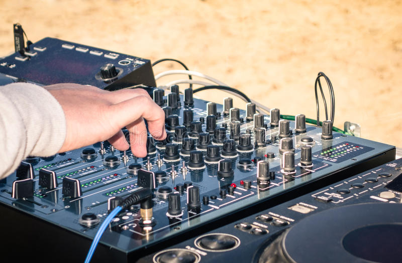 Hand av en deejay som spelar musik på yrkesmässig blandare royaltyfri foto