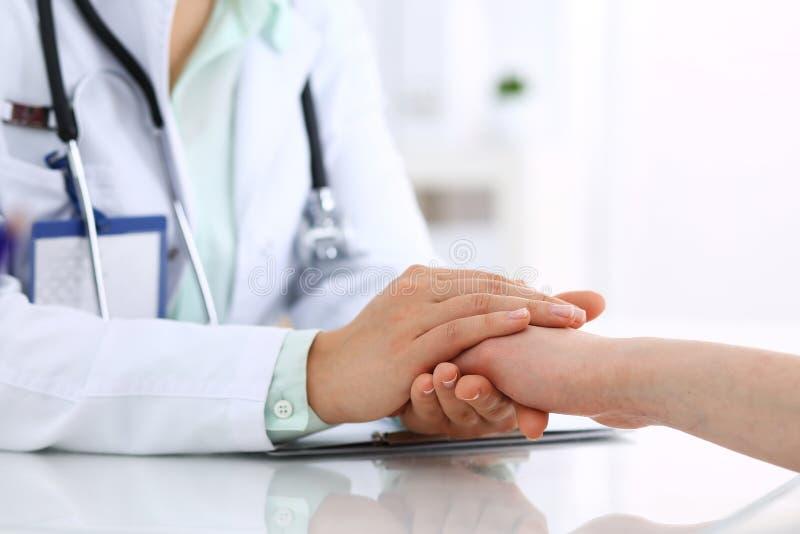 Hand av en doktorskvinna som uppmuntrar till den kvinnliga patienten, närbild Medicinska etik och förtroendebegrepp fotografering för bildbyråer