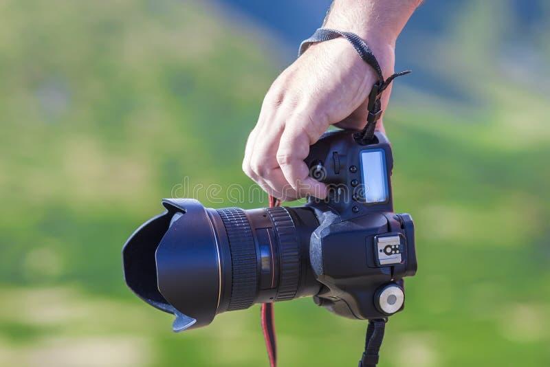 Hand av en hållande yrkesmässig digital kamera för man på suddig gre royaltyfria bilder