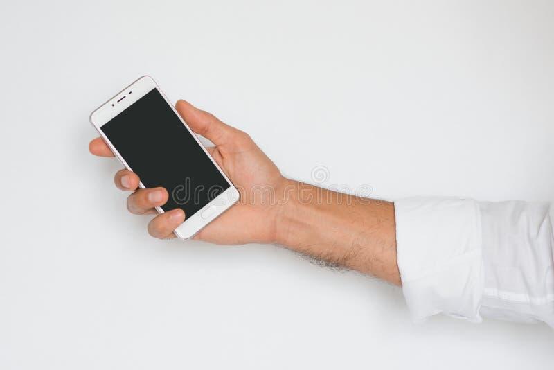 Hand av en man som rymmer den mobila smarta telefonen med svart skärm som isoleras på ljust - grå bakgrund fotografering för bildbyråer