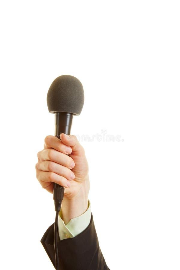 Hand av en reporter som rymmer en mikrofon royaltyfri bild