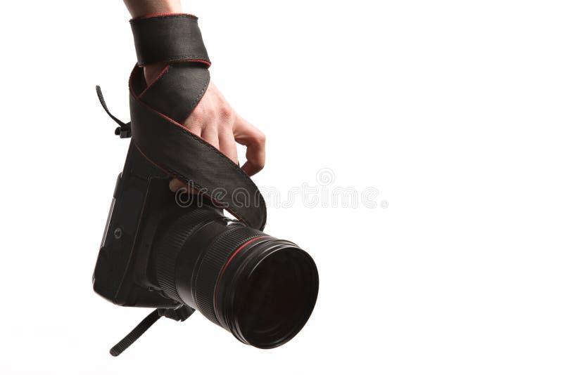 Hand av ett manslut upp med DSLR-fotokameran med fingret på slutaren på vit bakgrund royaltyfri bild