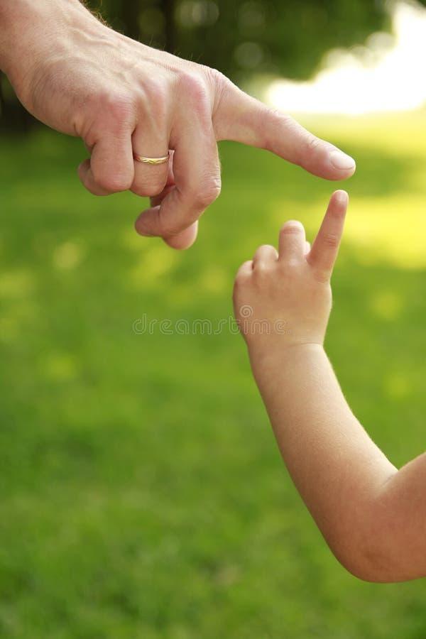 Hand av föräldern och barnet i natur arkivbild