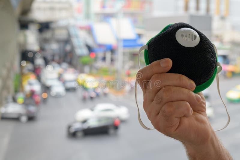Hand av för innehavframsida för hög man maskeringen för skydd från föroreningsmog i stad royaltyfria foton