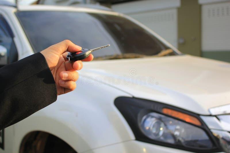 Hand av fjärrkontroll för maninnehavbil som pekar till den öppna bildörren, begrepp för system för bilsäkerhetslås royaltyfria bilder