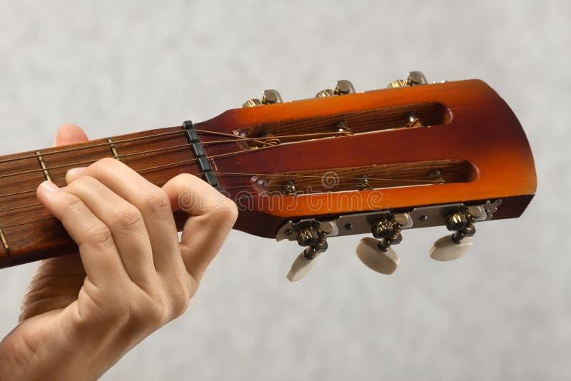 Hand av gitarristen som spelar den akustiska gitarren royaltyfri fotografi