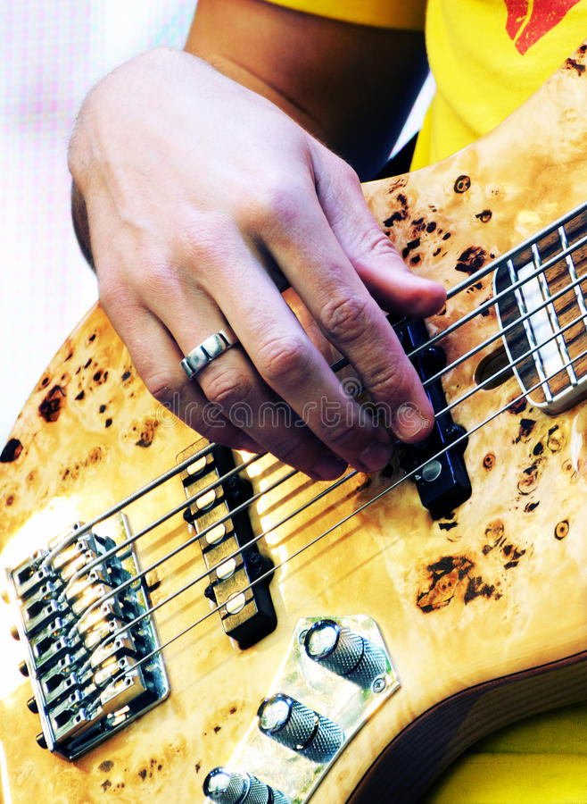 Hand av gitarristen som spelar den elektriska elbasen arkivbild