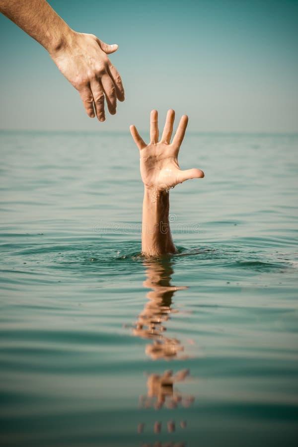 Hand av hjälp för att drunkna manlivbesparingen i havsvatten royaltyfria bilder