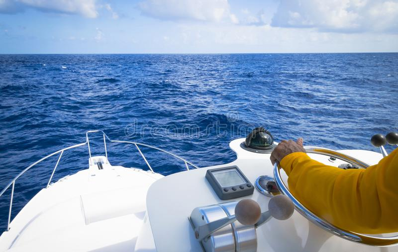 Hand av kaptenen på styrninghjulet av det motoriska fartyget i det förfallna blåa havet fiskeridagen royaltyfri fotografi