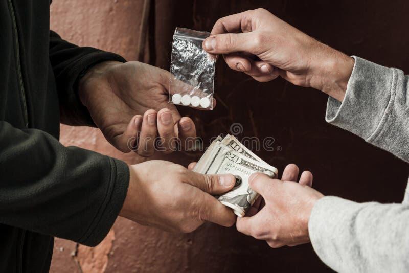 Hand av knarkaremannen med pengarköpandedosen av kokain eller hjältinnan royaltyfria foton