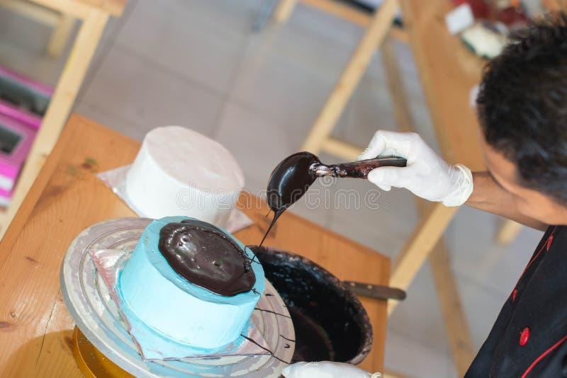 Hand av konditor som häller med smältt choklad på blå berrye arkivfoton