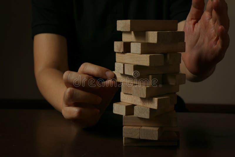 Hand av kvinnaplanläggningsrisken och strategi i affär Affärsman som spelar förlägga träkvarteret på ett torn och att skydda det arkivfoto