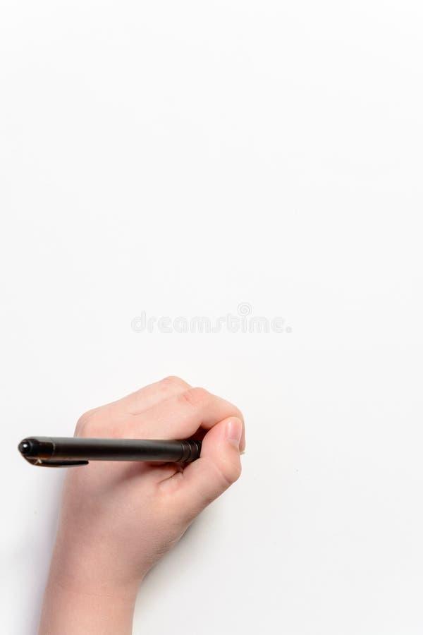 Hand av lite pojken med en svart penna på en vit bakgrund arkivbilder
