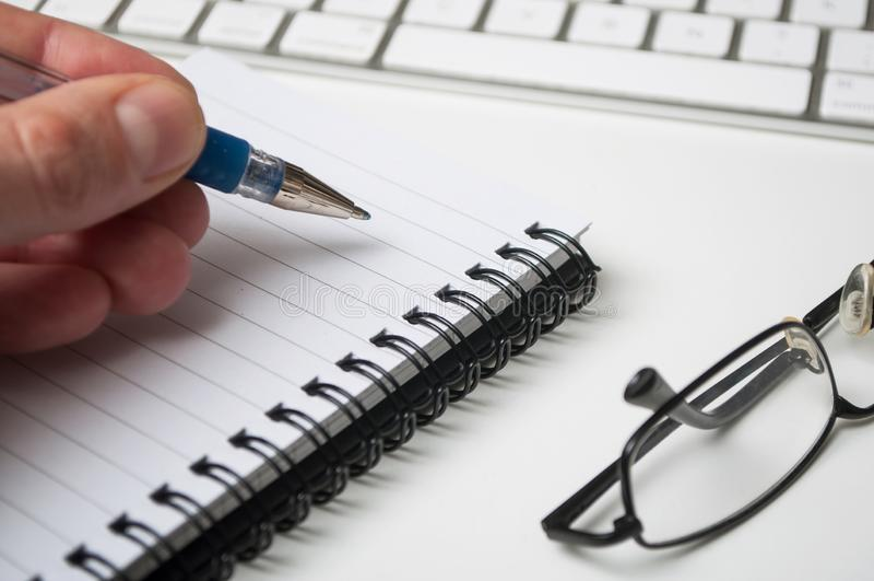 Hand av manhandstil med den blåa pennan på spiralesanteckningsboken på vit skrivbordbakgrund fotografering för bildbyråer