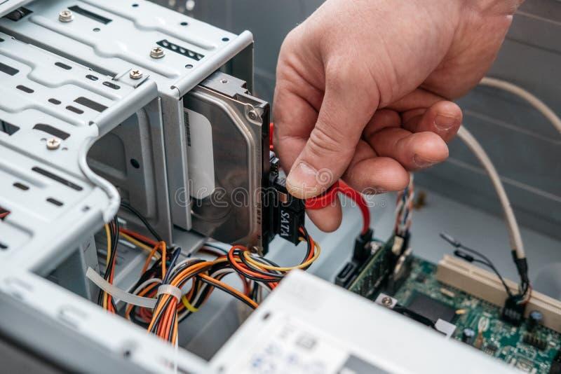 Hand av mannen som pluggar den SATA följetongen PÅ tillbehöret, Serial ATA datakabel i hårddiskapparat Datorbussmanöverenhet som  arkivbilder