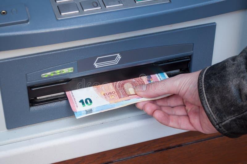 Hand av mannen som tar pengar på den automatiserade maskinen av arkivbild