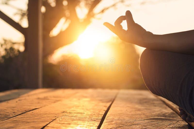 Hand av praktiserande meditationyoga för kvinna på natursolnedgång arkivbilder