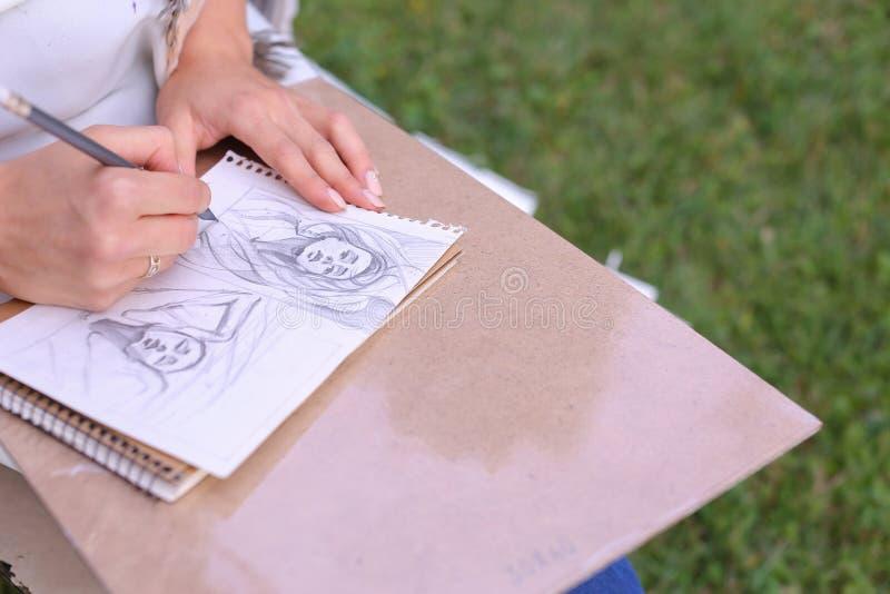Hand av slaglängder för flickakonstnärMakes Sure Sharp blyertspenna på albumet Pag fotografering för bildbyråer