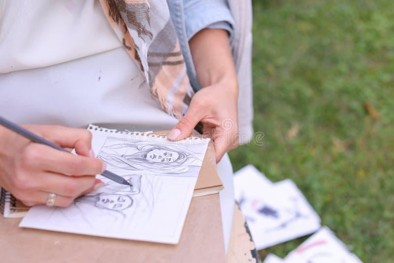 Hand av slaglängder för flickakonstnärMakes Sure Sharp blyertspenna på albumet Pag royaltyfria foton