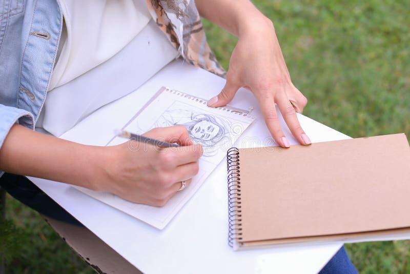 Hand av slaglängder för flickakonstnärMakes Sure Sharp blyertspenna på albumet Pag royaltyfri bild