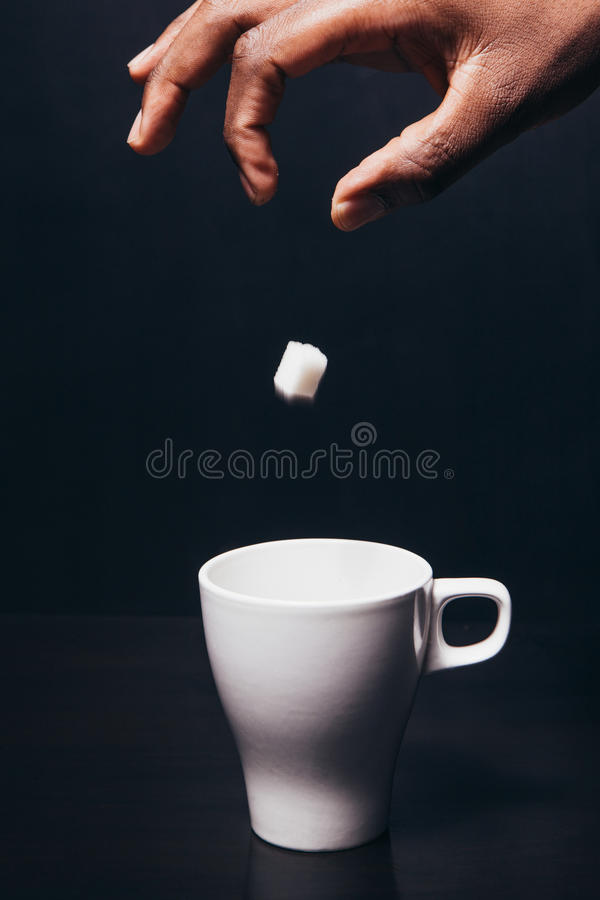 Hand av svart mandroppstycket av socker i den vita koppen royaltyfri fotografi