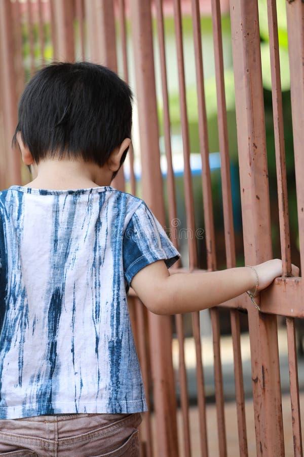 Hand av ungen på stålstaketdörren royaltyfri fotografi