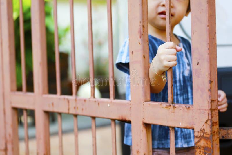 Hand av ungen på stålstaketdörren fotografering för bildbyråer