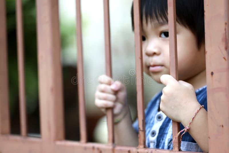 Hand av ungen på stålstaketdörren arkivbild