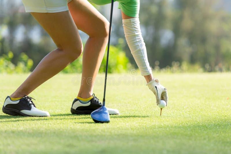 Hand Aziatische sportieve vrouw die golfbal op T-stuk met club in golfcursus zetten op avond op tijd voor gezonde sport royalty-vrije stock foto